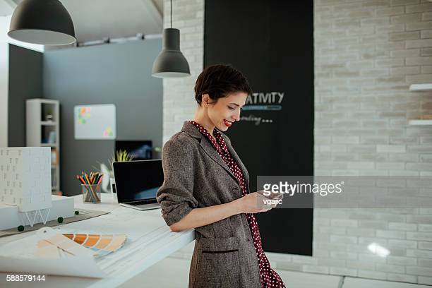 Female Architect Using Smart Phone In Her Office.