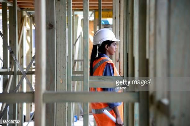SYD112017 Female Architect walking through house frame