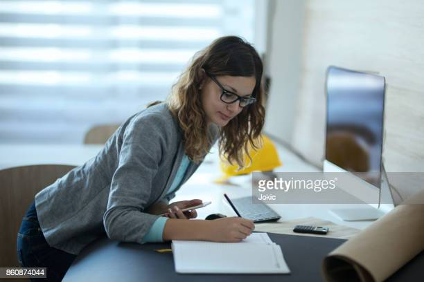Female architect writing down notes