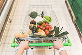 Top view close up woman hands pulling full shopping grocery cart in modern shop