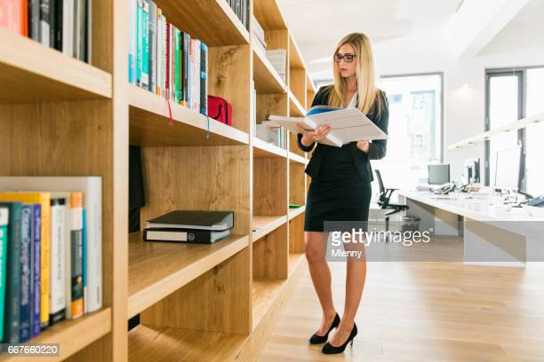 Female Art Director Designer reading Book for inspiration in modern office library