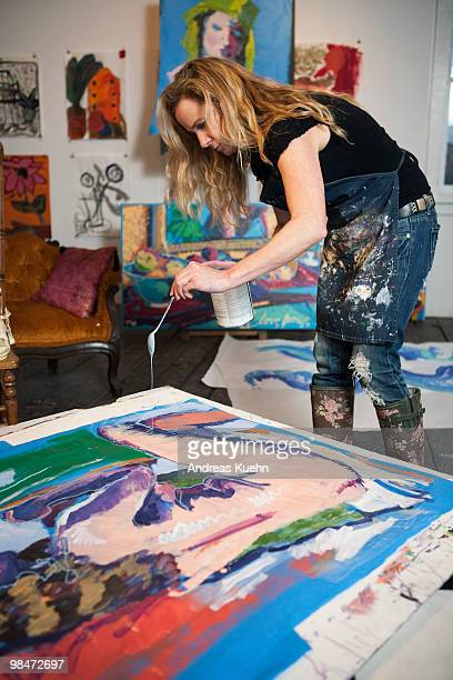 Female artist dripping paint onto her artwork.