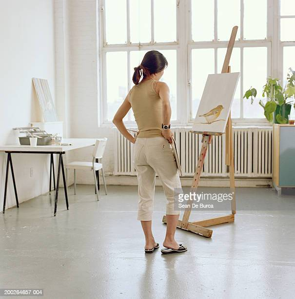 Female artist looking at painting on easel, rear view