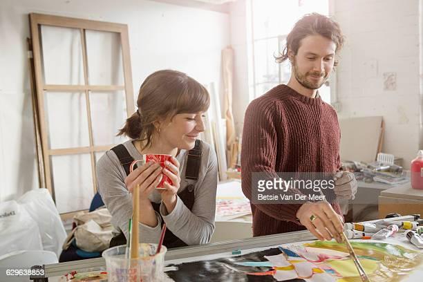 Female artist looks at artist finishing painting.