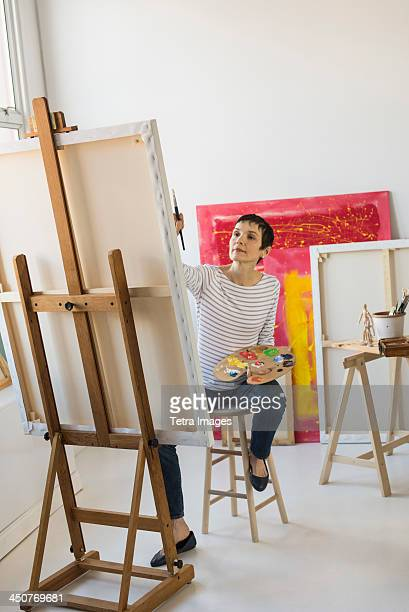 Female artist painting in her studio