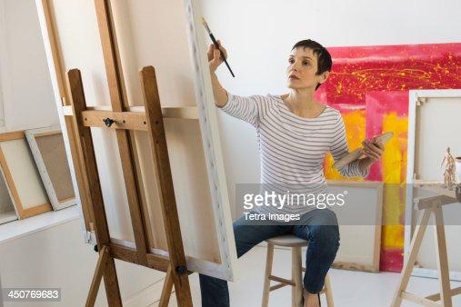 Female artist painting in her studio : Stock Photo