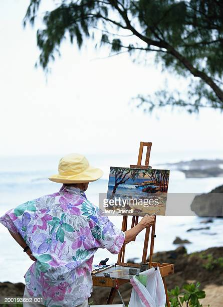 Female artist painting picture of beach, rear view