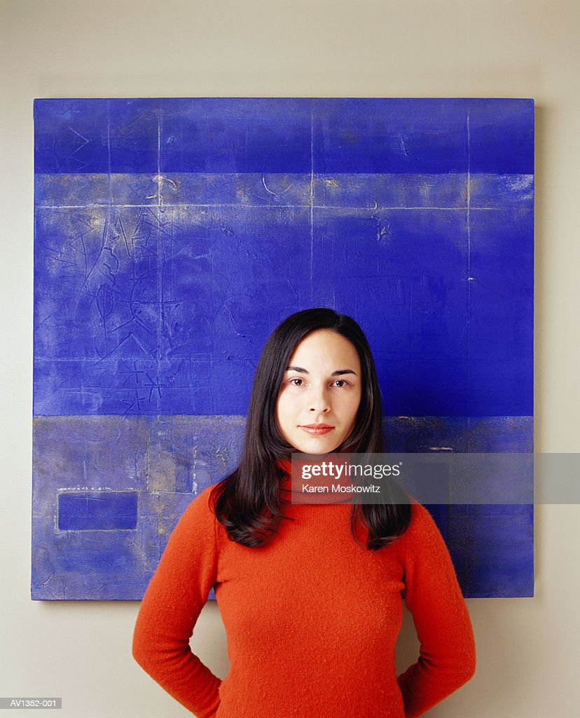 Female artist standing in front of artwork with hands behind her back : Stock Photo