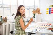 Female artist working on abstaract painting.