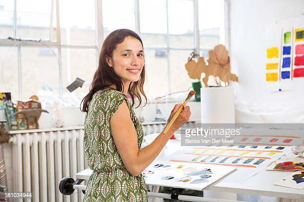 Female artist working on abstaract painting.