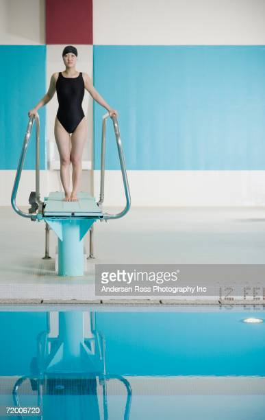 Female Asian swimmer on diving board
