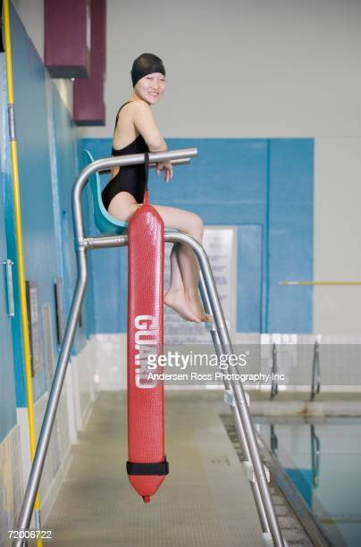 Female Asian swimmer on lifeguard chair