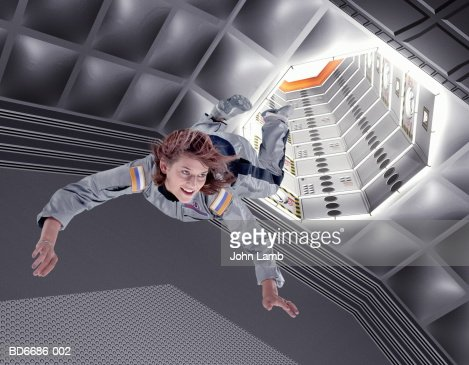 Female astronaut floating in space station (Digital Composite)
