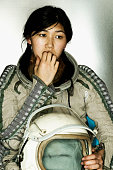 Female astronaut holding a helmet biting her finger nails