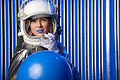 Female Astronaut Holding Blue Ball