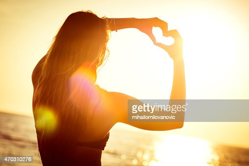 Female at the beach making a heart symbol with her hands
