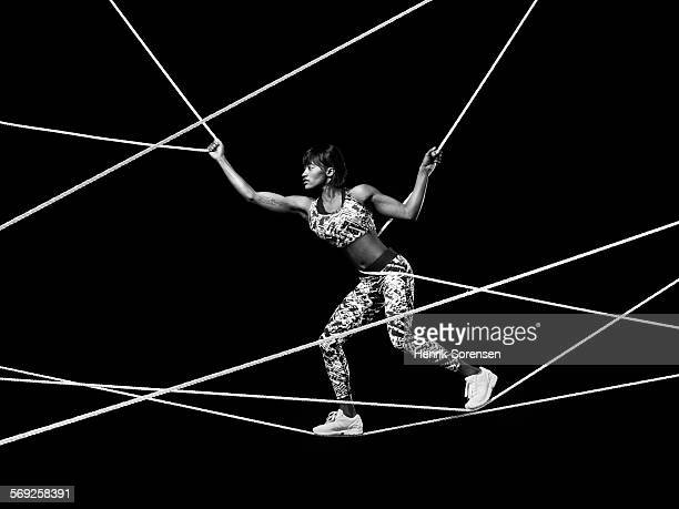 Female athlete balancing on ropes