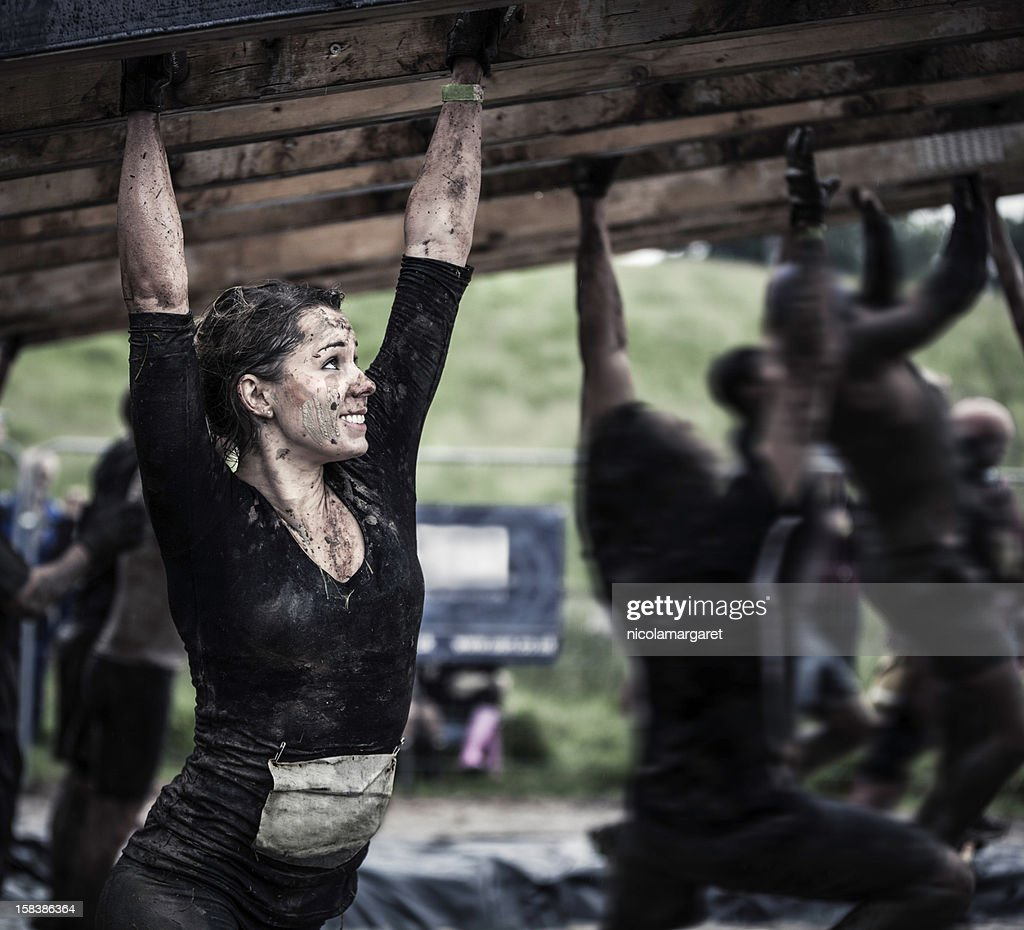 Female athlete competing in an obstacle course : Stock Photo