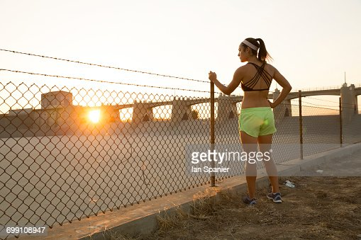 'Female athlete daydreaming by wire fence at sunset, Van Nuys, California, USA'