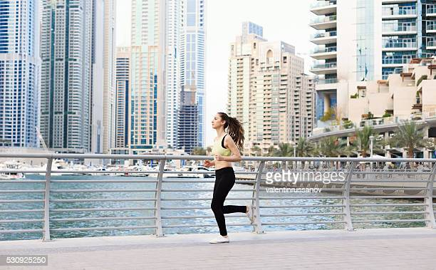 Female athlete doing jogging in Dubai Marina-side view