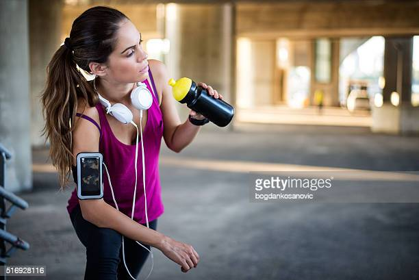 Female athlete drinking from sports bottle