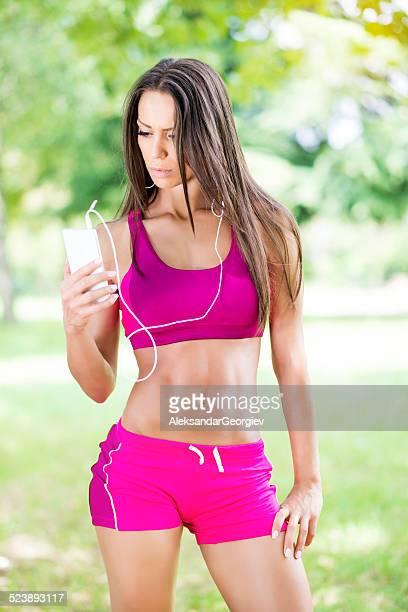 Athlète féminine exercice dans la Nature et peut accueillir un téléphone Mobile intelligent