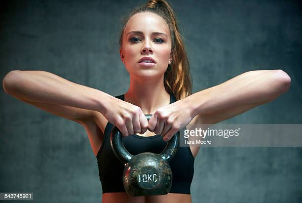 Female athlete exercising with kettle bell