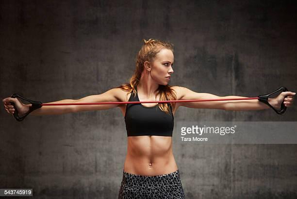 Female athlete exercising with stretch band