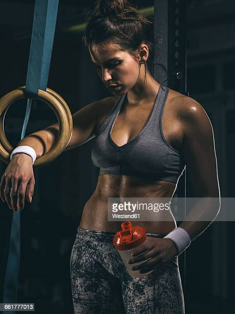 Female athlete, gymnastic rings and drinking bottle