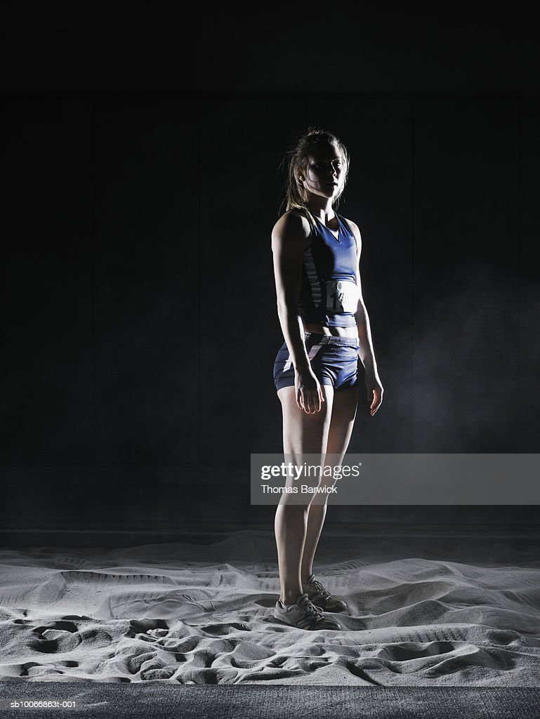 Female athlete in long jump pit, portrait : Stock Photo