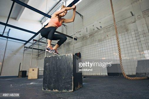 Mujer atleta se realiza caja jumps en el gimnasio : Foto de stock