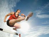 Female athlete jumping hurdle, Utah, United States
