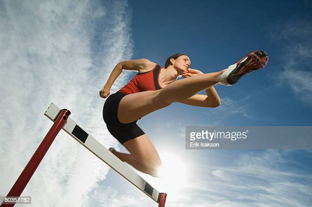 Female athlete jumping hurdle, Utah, United States