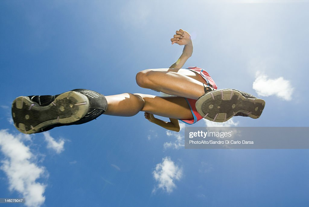 Female athlete jumping in air, directly below