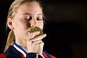 Female athlete kissing gold medal, portrait