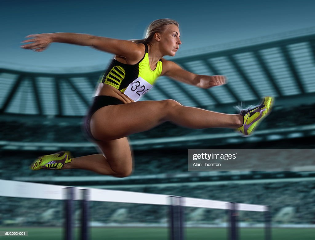Female athlete leaping hurdle, low angle view (Digital Enhancement) : Stock Photo