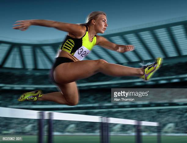 Female athlete leaping hurdle, low angle view (Digital Enhancement)