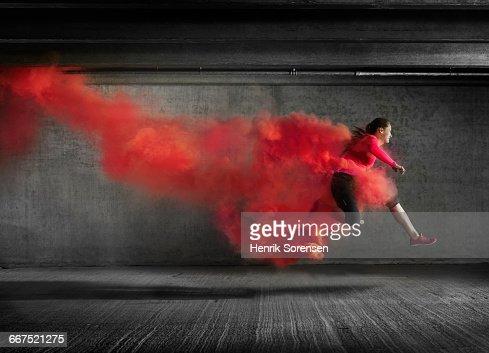 Female athlete leaping through smoke