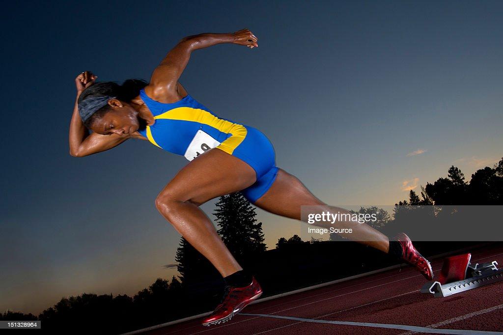Female athlete leaving starting blocks : Stock Photo