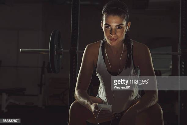 Female athlete listening to music on smart phone