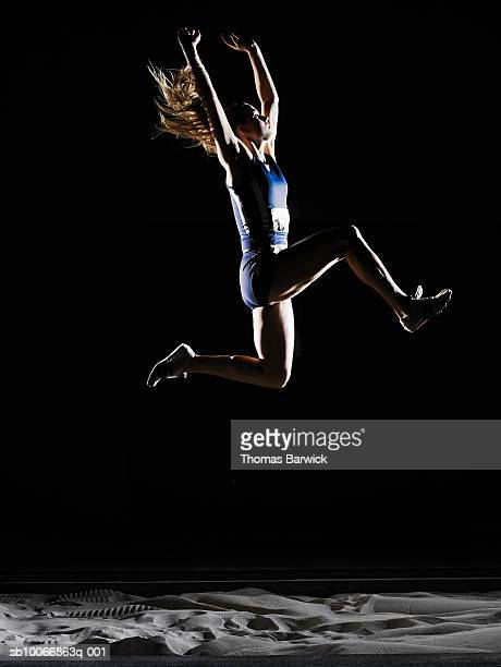 Female athlete long jumping, mid air