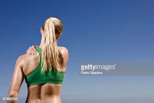 Female athlete massaging muscle tention. : Stock Photo