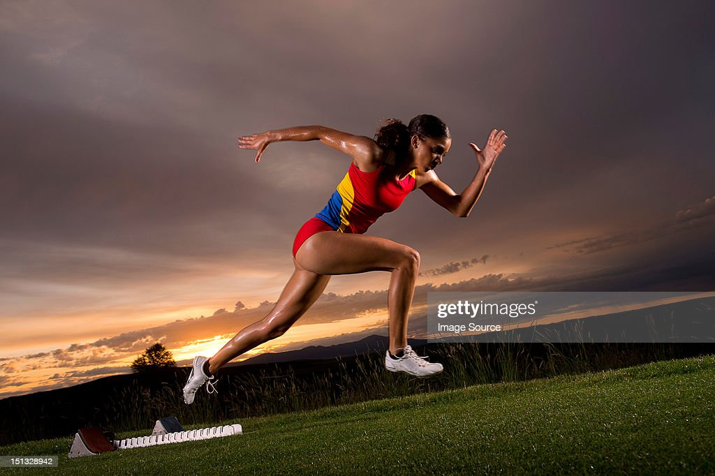 Female athlete moving off from starting blocks : Stock Photo