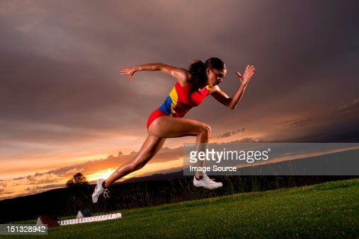 Female athlete moving off from starting blocks : Stock-Foto
