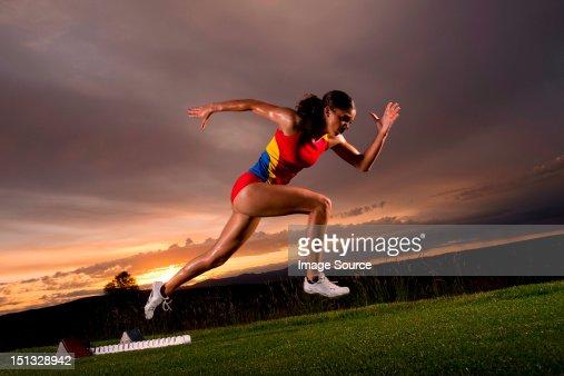 Female athlete moving off from starting blocks : ストックフォト