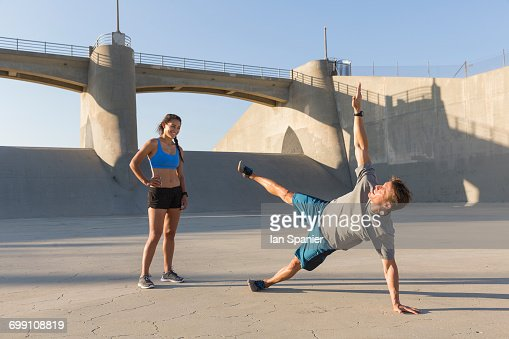'Female athlete observing friend workout, Van Nuys, California, USA'