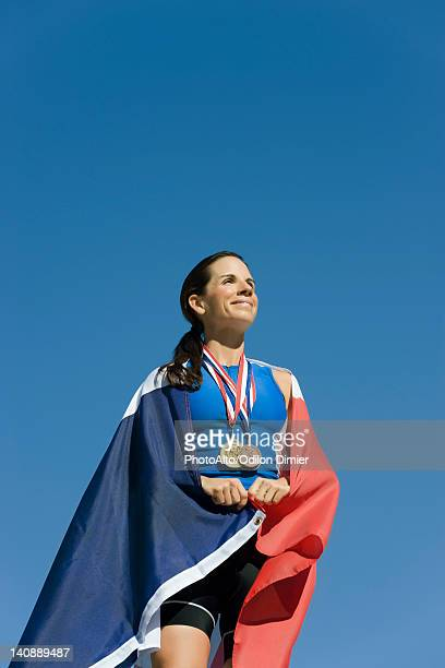 Female athlete on winner's podium, wrapped in French flag