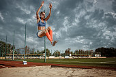 Female athlete performing a long jump during a competition at stadium. The jump, athlete, action, motion, sport, success, championship concept