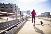 Young woman with headphones jogging outdoors in the morning. Her dog is making her company.
