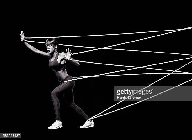 Female athlete pushing against ropes